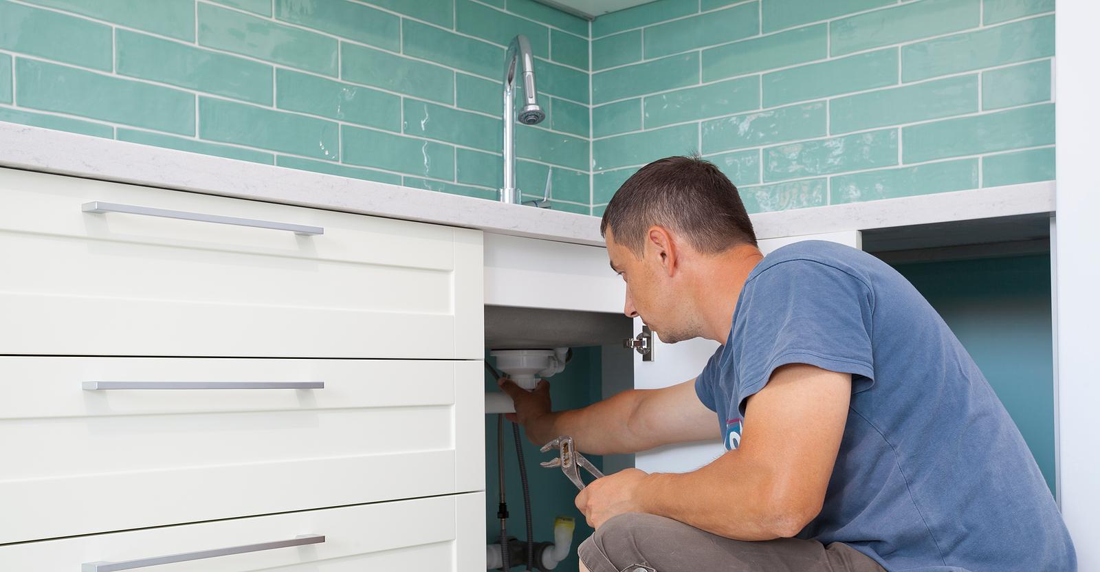 Plumber repairing the kitchen sink