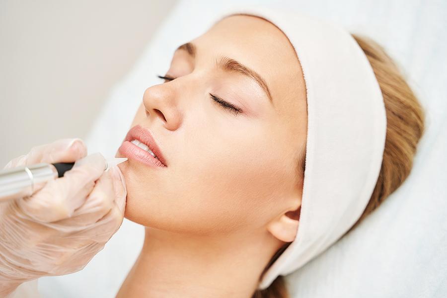 Woman getting a cosmetic lip tattoo