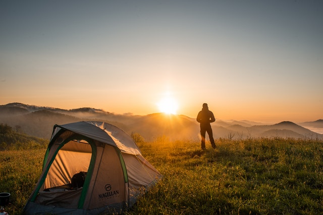 Hiking tent and a man standing from afar
